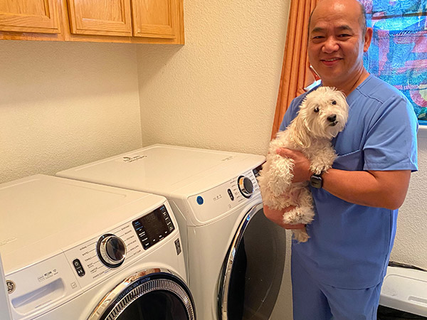 Nursing assistant Roland Cordova and dog pose for a photo next to his new washer and dryer pair.