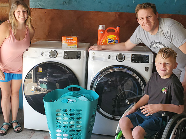 Nurse Ryan Bullock and family take a photo next to their new washer and dryer pair.