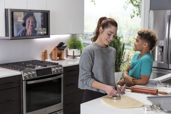 A woman cuts pie crust at a kitchen island while a young boy leans against it and video chats with his grandmother on a kitchen hub over the stove top behind them.