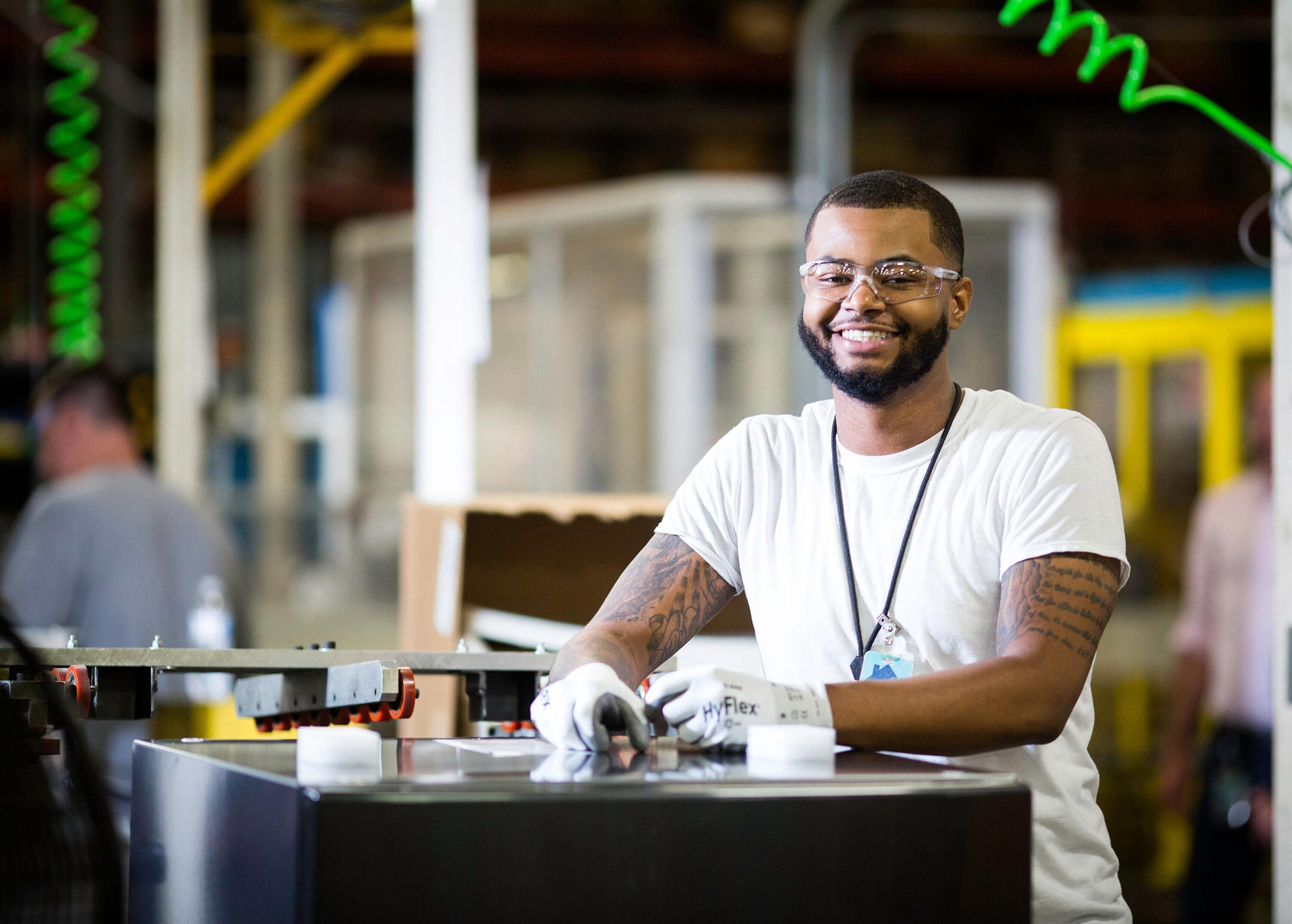 An employee smiles for the camera while wearing safety glasses and gloves in a GE factory.
