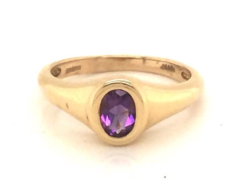 Bezel set oval amethyst ring.