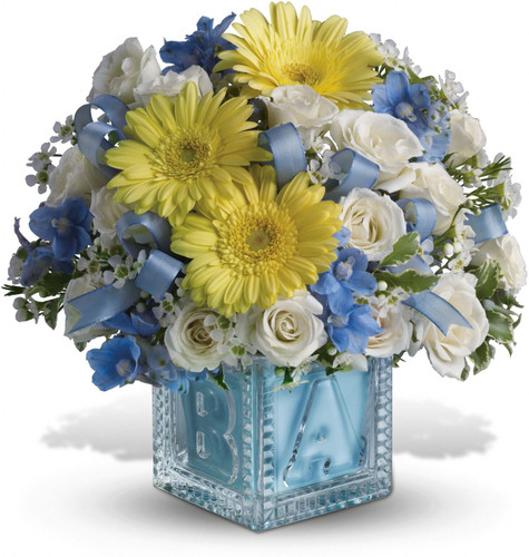 He'll be building block towers soon enough! For now, celebrate him with this beautiful keepsake baby block. Filled with soft blues and whites, the glass block can be used later in baby's room and makes a memorable baby boy gift. A baby blue ribbon weaves through white spray roses and blue delphinium in a keepsake glass baby block vase. Orientation: All-Around