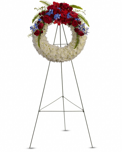An elegant ring of serene white flowers topped with bold red and blue blooms is a strong and loving tribute to a life distinguished by patriotism, honor and dedication to country. A distinctive sympathy wreath of traditional flowers such as red roses and gladioli, bright white chrysanthemums, and proud blue hydrangea and delphinium. Orientation: One-Sided