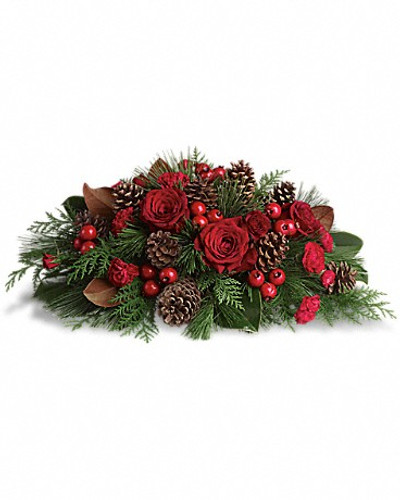 "Gorgeous red roses and spray roses, berry sprays and carnations are arranged with pinecones and festive greenery. A great way to serve up holiday cheer! Approximately 22"" W x 11"" H"