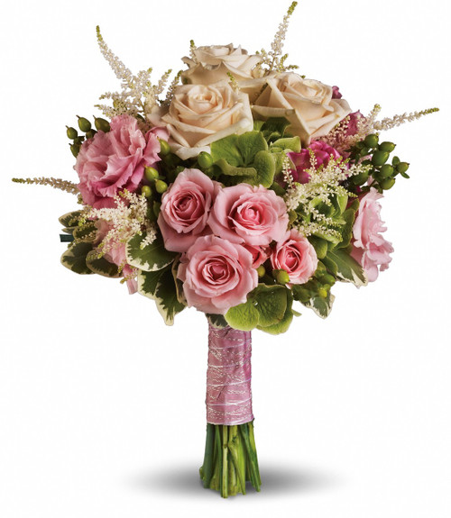"""A lovely ensemble of pink roses, white astilbe, green hypericum and hydrangea with variegated pittosporum. Approximately 11"""" W x 14"""" H"""