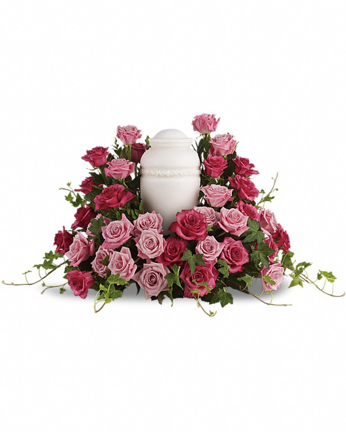 Surrounded by roses, enveloped in love - a sumptuous pink rose wreath of light and dark hues serves as a stunning memorial. Features thirty five light and hot pink roses with trailing stems of lush green ivy.Please note: Arrangement does not include urn. Orientation: One-Sided
