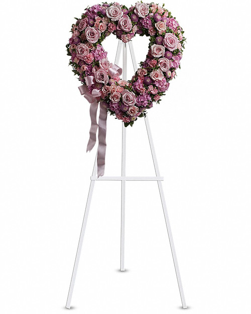In the shape of a heart, and accented with a pink satin ribbon, this garden of delicate blooms is a tender and classic tribute to a precious life, and a cherished expression of love and sympathy. Beautiful flowers such as light pink roses, hydrangea and miniature carnations mix with lavender chrysanthemums on an open heart-shaped wreath. Orientation: One-Sided