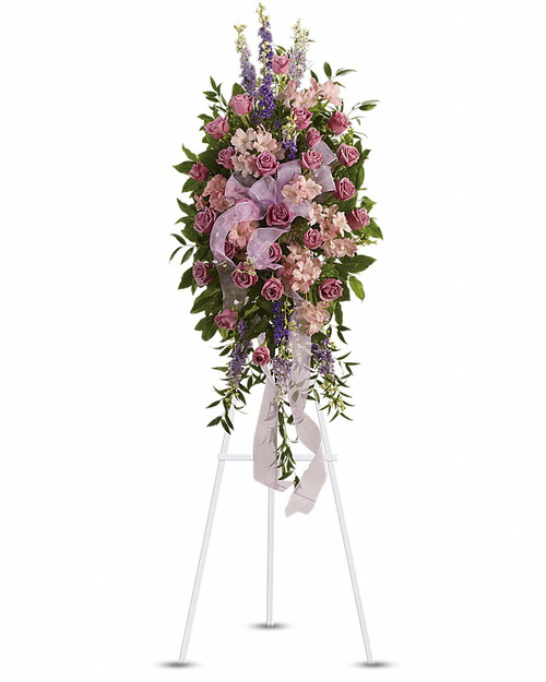 This abundant spray of soft, feminine spring colors feels as calming as a walk in the countryside. Sheer organza ribbon is threaded through lavender, purple and pink blooms that are accented by trailing greens. Includes soothing flowers such as lavender roses and larkspur, plus pink alstroemeria. Orientation: One-Sided