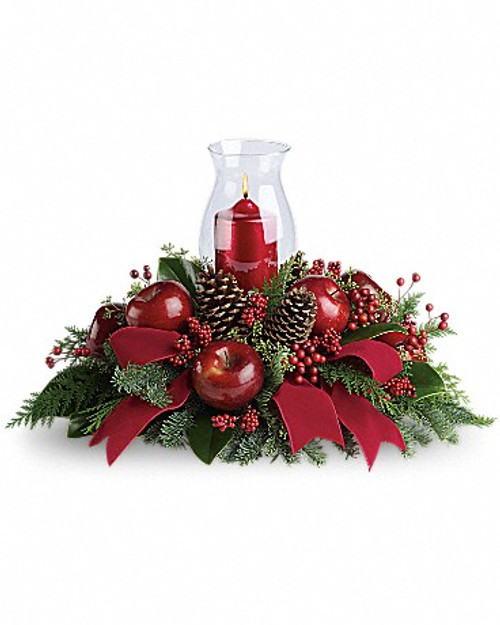 "Brilliant red berries and apples are delivered with an elegant hurricane candle, pinecones, winter greens and a stunning red velvet ribbon. It brings a lot of elegance to the table! Approximately 23"" W x 15 1/2"" H"