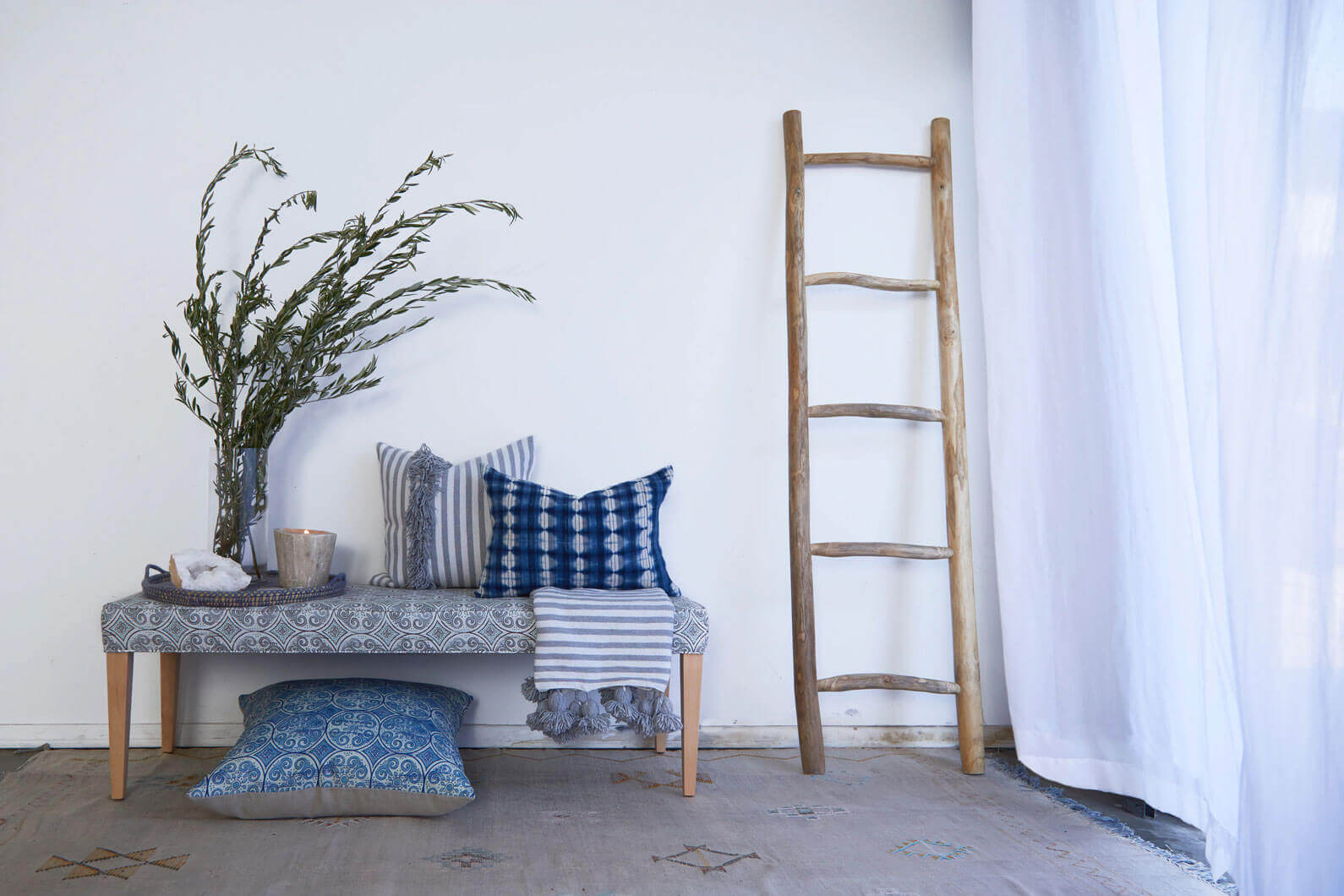 Bench with throw pillows next to wooden ladder