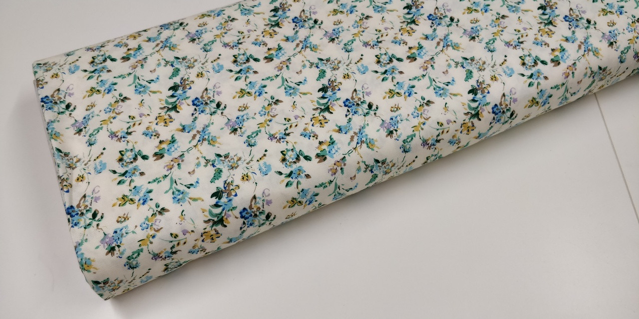 A lovely cream with turquoise flowers 100% brushed cotton fabric,  Would look superb made into dresses or blouses, Would work well with rice imperial broadcloth smocked insert,  146cm wide,  Wash at 30 degrees  Priced per metre,  Telephone for part metres