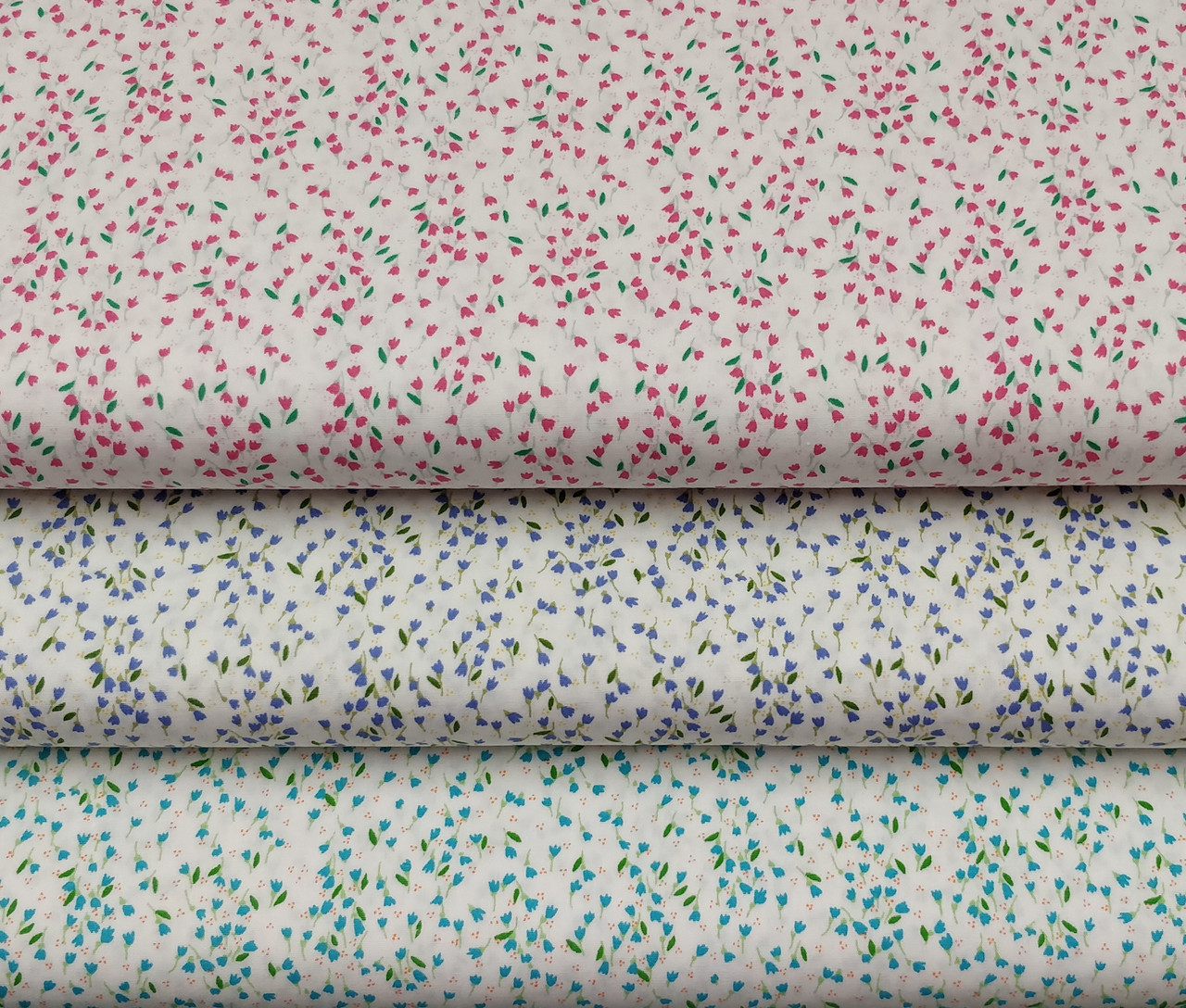 """A lovely quality cotton print in two colours, white background with pink, lavender or turquoise flower design, 100% cotton, 45"""" 110 cm wide, Ideal for smocking projects, Wash at 30 degrees, Priced per metre"""