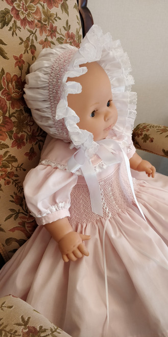A Ready to Smock Bonnet kit, Kit includes, Pre-pleated lace edged , bonnet, Ribbon for the ties, Ribbon for the back casing, Two poinsetta flower decorations, 1 x crewel needle, DMC thread in pink 3689,  Smocking instructions, Smocking stitch guide, Smocking stitch tips, Smocking graph