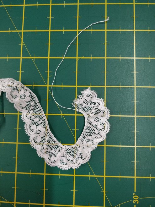 Flower and spot design edging lace in white 2.2 cm wide - shown using gathering thread in the lace