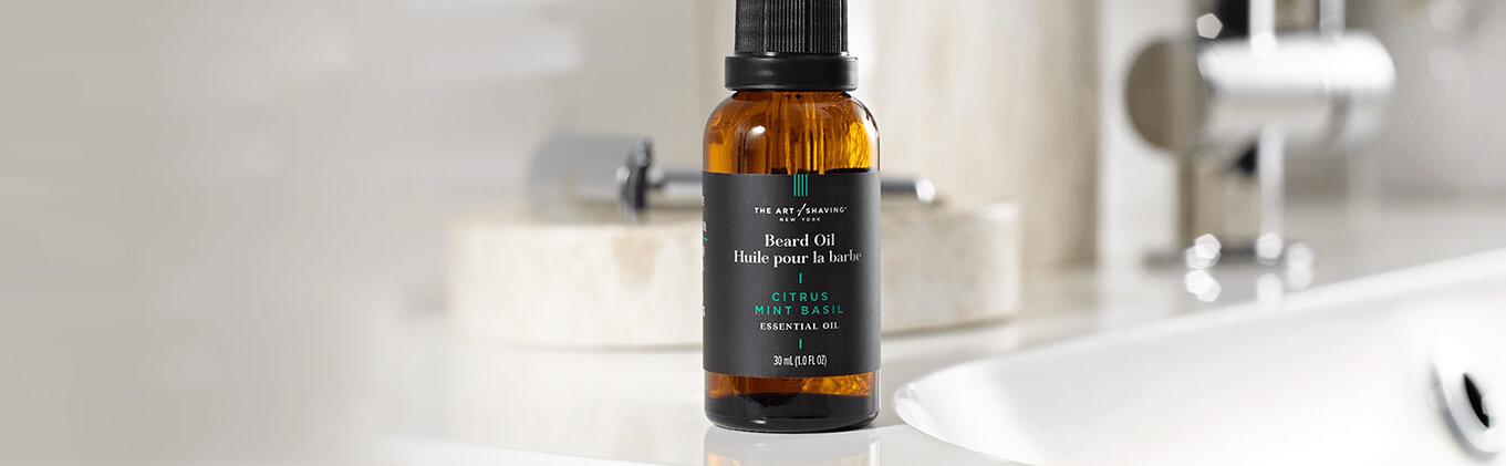 A bottle of The Art of Shaving Citrus Basil Mint Beard Oil on a bathroom counter.