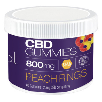A small plastic jar of peach colored and flavored gummy worms with CBD.