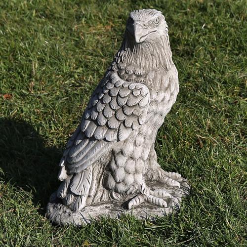 A stone eagle, bird of prey, statue, a garden ornament.