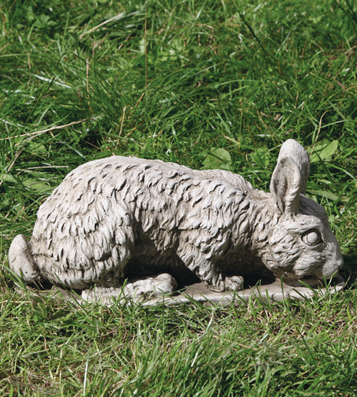 A stone bunny rabbit statue, a garden ornament.