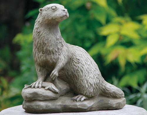 A detailed stone otter statue, a garden ornament.