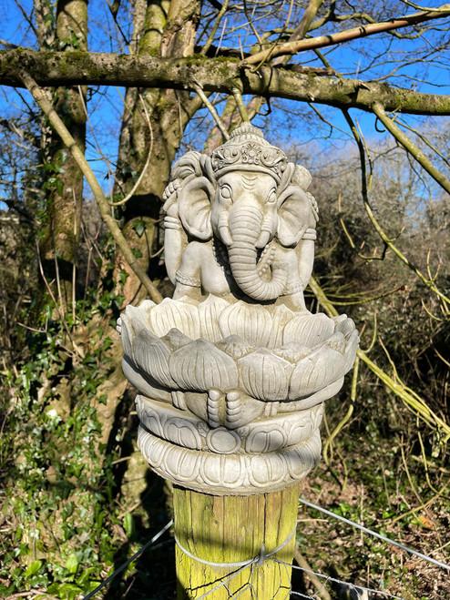A large stone bird feeder shaped like the Oriental God Ganesh.
