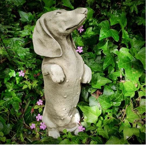 A stone garden ornament statue depicting a dachshund dog puppy.
