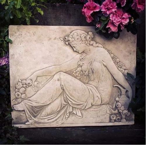 A stone plaque in  an Art Nouveau style, a garden ornament.