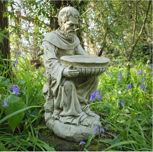 A stone bird bath in the shape of St Francis, a garden ornament.