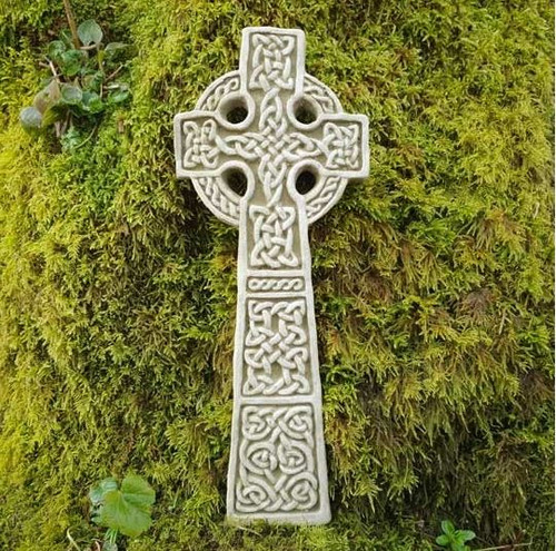 A stone Celtic Cross wall hanging. A garden ornament.