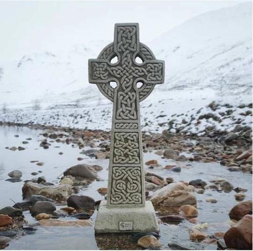 A stone Celtic Cross statue. A garden ornament.