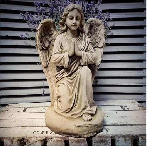 A detailed stone angel statue. A garden ornament.
