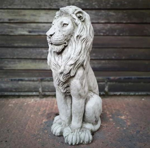 A large, detailed stone statue of a lion. A garden ornament.