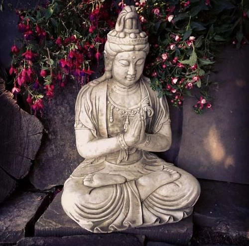 A large, detailed stone statue of a buddha. A garden ornament.