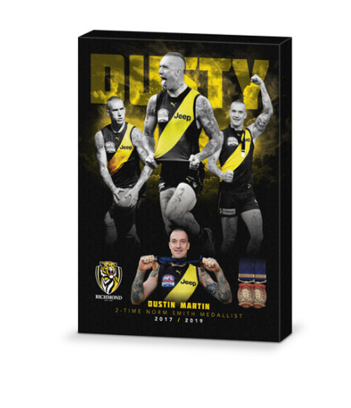 A 57cm by 42cm black based canvas celebrating Dustin Martins 2017 and 2019 Norm Smith wins. Dusty displayed in yellow block letter across the top of the canvas followed below by 3 coloured images of Dustin, as well as photos of both Norm Smith medals at the bottom.