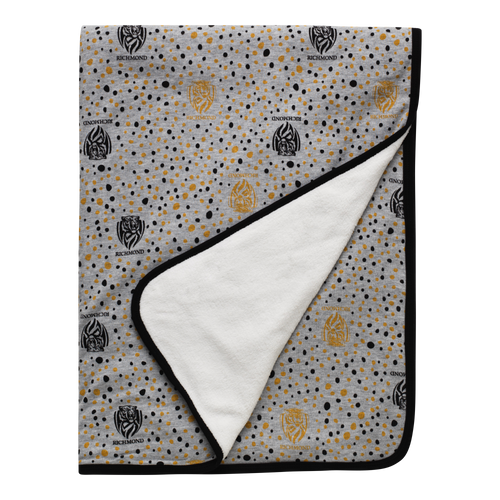 A Grey based baby blanket with black piping along the outside of the blanket. Displayed on it are a mix of black and yellow dots along with the Richmond Club logo.