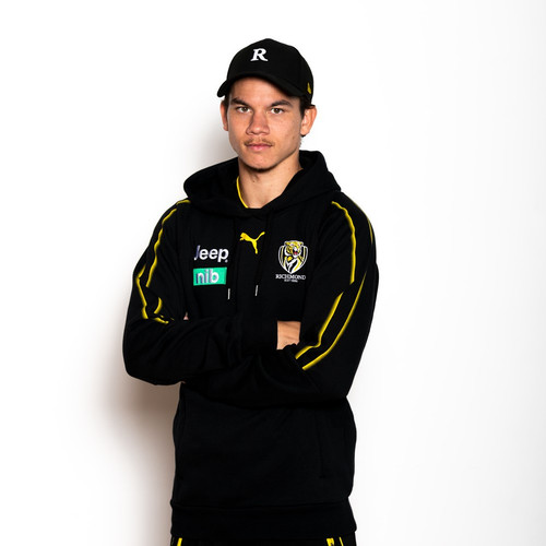 """Plain black cap with a white letter """"R"""" on the front. New Era symbol in yellow on the side and on the adjustable strap a yellow square with the number 17 (for Daniel Rioli). This cap also has a small part of Daniels Dreamtime design on the side."""