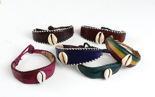 "Single Cowrie Shell Bracelet on Wide Leather Band. Genuine leather bands, handcrafted and skillfully stitched along the borders, with a single cowrie shell in center. During the reign of kingdoms in Africa cowrie shells were valued as a form of money. Own your own piece of history with one of these bracelets, available in several colors 3"" wrist opening and are 8"" in length.    Note: The reds may come in solid or with stripes, as there are different variations available. Do not untwist the closure this will prevent the bracelet from opening during wearing. Handmade in Nigeria."