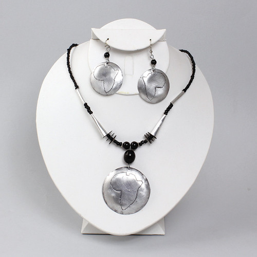 """Black beaded necklace with a twist clasp to ensure comfort, silver cylinders lead to the pendant itself which is a brushed metal disc showcasing the outline of Africa. 19.5"""" long. 2"""" pendant. 1"""" earrings."""