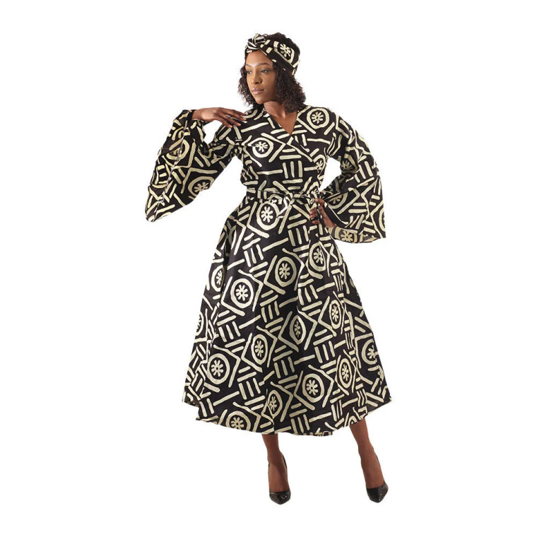 """Stylish and feminine, this Mud Print Wrap Dress makes a regal addition to any wardrobe. The wrap dress has a V-neck, long bell sleeves, ties at the waist, and has an A-line skirt that falls below the knee. It is black with a pattern of traditional mud print designs in a cream color. Comes with a matching head wrap. The dress is 52"""" in length. The sleeves are 22"""". It will fit up to a 50"""" bust. Made in India of 100% cotton.  Made in India The dress is 52"""" in length. The sleeves are 29"""". It will fit up to a 50"""" bust."""