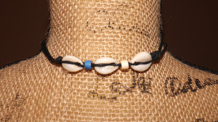 """Single Strand Cowrie Shell Choker  Single strand cowrie shell choker with a 14"""" circumference...adjustable. Ideal for men and women.  Color choices: Blue, Blue/White, White.   Made in India."""