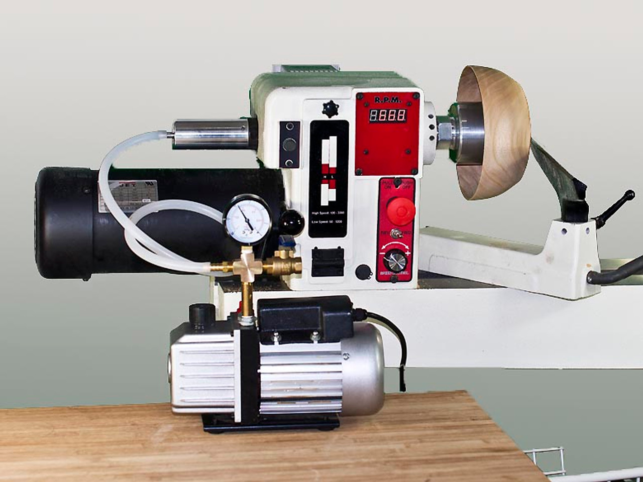 Vacuum chuck shown on a wood lathe with manifold kit and vacuum pump.