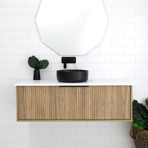 Marquis Cove 1200mm Wall Hung Vanity in Prime Oak cabinet finish, Symphony Blanco top, matte black paco basin, and matte black top-pull handle. Featured with the Marquis 900mm Deco mirror.