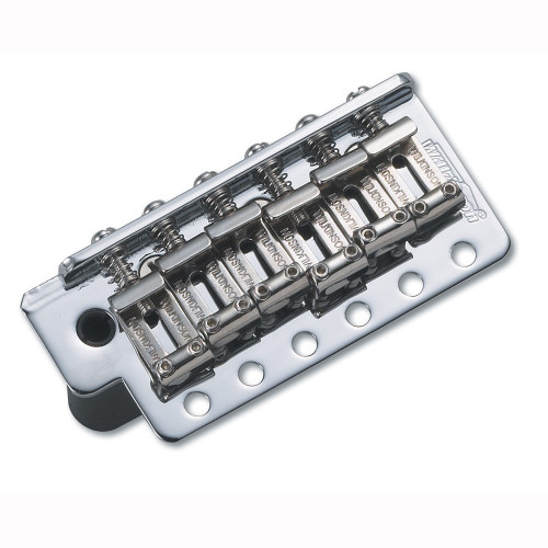 """Since its introduction in 1954, this classic design is the most copied guitar vibrato bridge ever.  The design is so simple and eminently usable it is a challenge to improve on it, but improve it we did!  Faithfully reproducing the size and weight of the original, this is a direct retro-fit for the """"real thing"""" but with the added benefit of a push-in vibrato arm (rather than the troublesome original screw-in type).  We also staggered the string holes in the sustain block allowing the strings to follow the natural intonation line of the saddles, keeping the strings' """"angle of attack"""" over the saddle's intonation point more consistent, eliminating annoying string """"hang-up"""" giving unrivalled tuning stability.  Completing the assembly are the bent steel saddles built from the same gauge steel as the originals to retain the """"vintage sparkle"""" that this bridge has become famous for."""