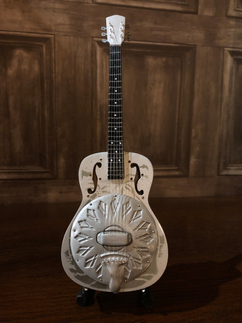 <p>In stock and ready to ship at MorMusic</p><p>Seen it cheaper elsewhere? We'll aim to match or beat any like for like price!</p><p>Highly collectible hand-made miniature resonator guitar.</p> <p>Mini Guitar 1:4 scale model replica - original gift idea and cool music gadget - material: Balsa wood - hand made and hand airbrushed - miniature size cm: 8,5 x 27,5 x 1 - guitar stand included.</p> <p>*Model names and artist names are used for look-alike examples only. Some famous names are used to depict the style of each type of instrument. None of the instruments on this website are exact replicas in proportions, sizes and design. All the products are hand made and hand airbrushed and are not made by industrial processes. Products for collection or for decoration only, they are not toys.</p>