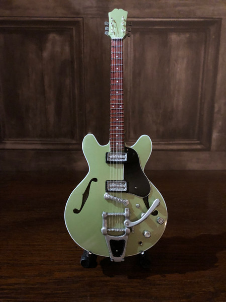 <p>In stock and ready to ship at MorMusic</p><p>Seen it cheaper elsewhere? We'll aim to match or beat any like for like price!</p><p>Highly collectible hand-made miniature guitar in metallic green.</p> <p>Mini Guitar 1:4 scale model replica - original gift idea and cool music gadget - material: Balsa wood - hand made and hand airbrushed - miniature size cm: 8,5 x 27,5 x 1 - guitar stand included.</p> <p>*Model names and artist names are used for look-alike examples only. Some famous names are used to depict the style of each type of instrument. None of the instruments on this website are exact replicas in proportions, sizes and design. All the products are hand made and hand airbrushed and are not made by industrial processes. Products for collection or for decoration only, they are not toys.</p>