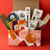 Contents of the Chocolate Adventure gift box in giftable box on orange background