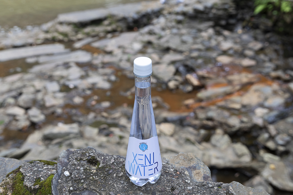 XENI WATER bottle made by Bubble Sip LLC on a rock