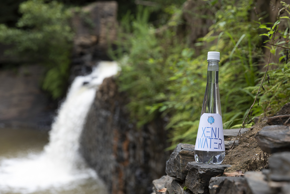 XENI WATER bottle made by Bubble Sip LLC on a rock in front of a waterfall
