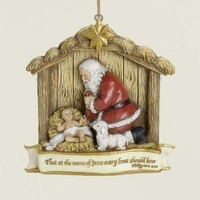 Kneeling Santa Claus Christmas Tree Ornament.  Features Santa kneeling beside the baby Jesus inside the nativity stable .