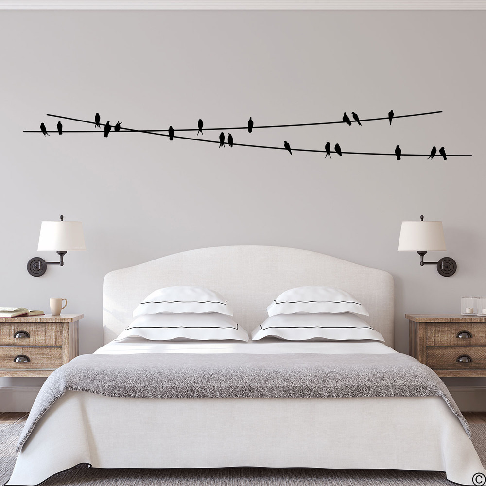 """The """"Birds On Wire"""" wall decal placed above a bed in black vinyl color."""