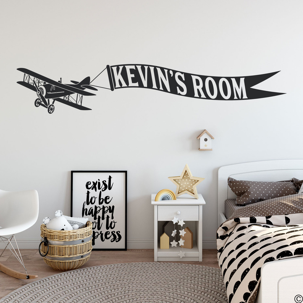 Biplane wall decal with customizable name banner on a kids bedroom wall in black vinyl.